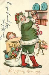 CHRISTMAS GREETINGS  green suited Santa fills stocking, girl peeks, sack of toys below