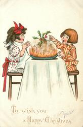 TO WISH YOU A HAPPY CHRISTMAS  two children are surprised by holly on top of Xmas pudding