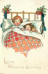 LOVING CHRISTMAS GREETINGS  two children & doll in bed, Xmas stockings & holly on bed-head