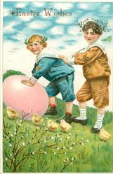 two boys roll giant Easter egg up hill, 5 chicks & pussy-willow below