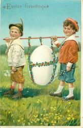 two boys walk left carrying giant white egg slung from a pole