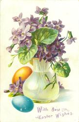 violets in green tinted glass vase, yellow & blue eggs left