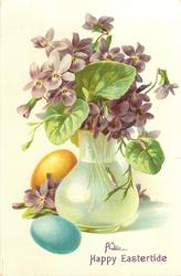 violets in tall cream coloured vase & on ground, blue, purple & yellow eggs right