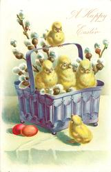 three chicks with pussy-willow in purple basket on wall, another sits on handle, another on ground, 2 red easter eggs