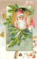 LOVING CHRISTMAS GREETINGS circular inset of red-coated Santa in front of evergreen, blowing snow around, nuts & apples below