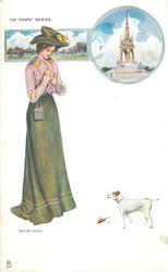 pretty girl in green looks down at terrier who has brought small dead bird, insert of Albert Memorial above