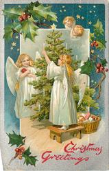 CHRISTMAS GREETINGS  two angels in white decorate tree