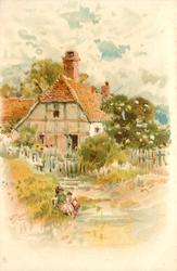 woman & child sit on ground left of path, fence & cottage behind