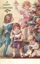 A HAPPY CHRISTMAS, four girls decorate tree, girl on right sits on floor & plays with toy bird