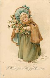 TO WISH YOU A HAPPY CHRISTMAS  young girl in green coat, brown/blue cape stands in snow holding holly
