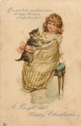 A BRIGHT AND HAPPY CHRISTMAS  seated girl plays with kitten on her lap