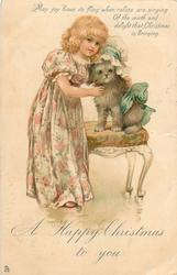 A HAPPY CHRISTMAS TO YOU  girl in floral dress, caresses dressed puppy on chair
