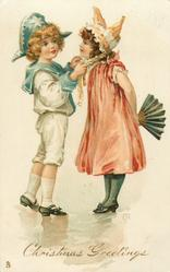 CHRISTMAS GREETINGS, boy adjusts hat ribbon of girl who has fan held behind her