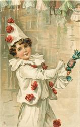 boy in pierrot costume holds out a cracker, faces right, dancers in background
