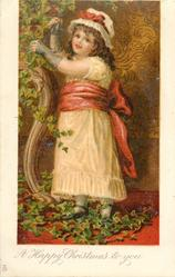 A HAPPY CHRISTMAS TO YOU  full length study of girl in white dress & red sash adjusts ivy left, facing left looking front