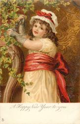 A HAPPY NEW YEAR TO YOU  three quarter length study of girl in white dress & red sash adjusts ivy left, facing left looking front