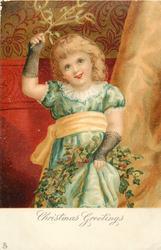 CHRISTMAS GREETINGS  three quarter length study of blonde girl holding mistletoe over-head, holding up dress, wearing fish-net black gloves