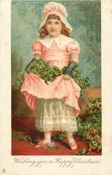 WISHING YOU A HAPPY CHRISTMAS  girl in pink dress stands facing front holding ivy in her skirt, more on ground