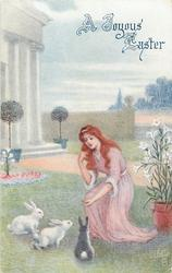 A JOYOUS EASTER  woman in pink feeds three rabbits on lawn