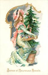 BONNE ET HEUREUSE ANNEE woman in green/pink holds basket of tree ornaments
