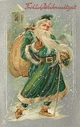 FROHLICHE WEIHNACHTSZEIT full length green-robed Santa with cane in left hand, bag over shoulder