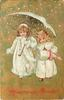 HEUREUSE ANNEE  two girls in white coats under umbrella in snow, one wears muff