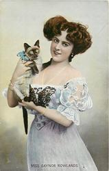MISS GAYNOR ROWLANDS  standing holding Siamese cat, looks front