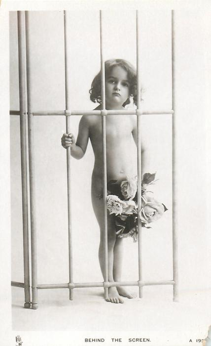 BEHIND THE SCREEN  young nude girl stands behind trellis holding bunch of roses, facing front, looking front