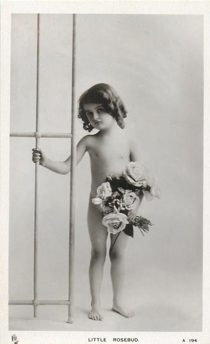 LITTLE ROSEBUD  nude young girl holds on to trellis with one hand, roses in the other