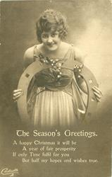 THE SEASON'S GREETINGS, girl stands facing front bent over holding fake horseshoe & mistletoe