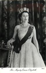 HER MAJESTY QUEEN ELIZABETH  standing, arm on chair facing & looking front