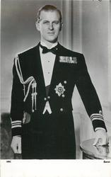 Prince Phillip in naval uniform, left hand on table