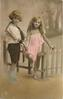 boy and girl stand by picket fence.  girl is partially sitting on the fence