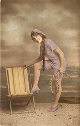 girl in bathing suit on the beach facing left, looking front, right foot up on deck chair, rope in left hand