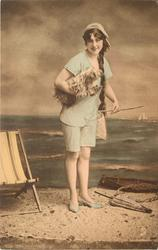 girl in bathing suit on the beach with fluffy dog under her right arm, deck-chair to left