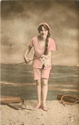 girl on beach holding handle of net with right hand, supports it with her left, looking front, no deck chair