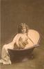 young girl sits in portable bath tub, facing right & looking forward, holding stuffed rabbit under her right arm