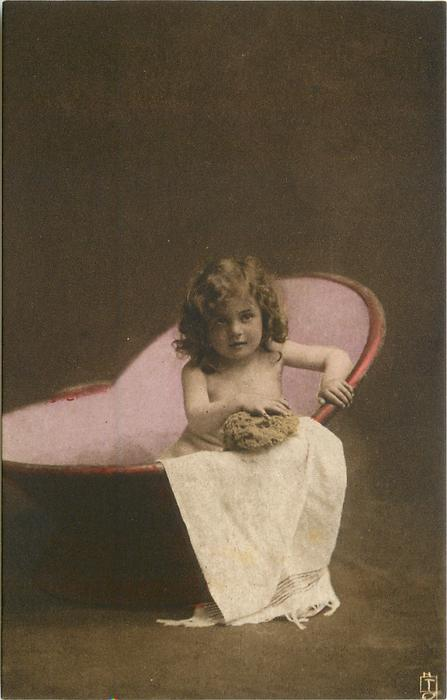 young girl sits in portable bath tub, facing & looking forward, sponge directly in front held with both hands