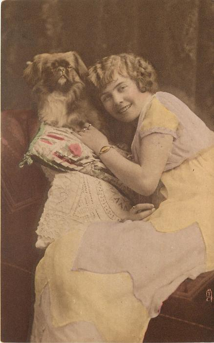 young lady sits looking forward facing left, left hand touches pekingese dog sitting up on pillow by her face