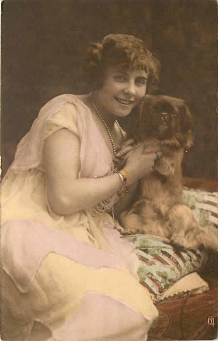 young lady sits looking forward facing right, right hand supports pekingese dog sitting up on lap