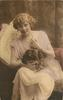 young lady sits looking & facing forward, left hand touches pearls, holding pekingese dog on lap, dog looks up