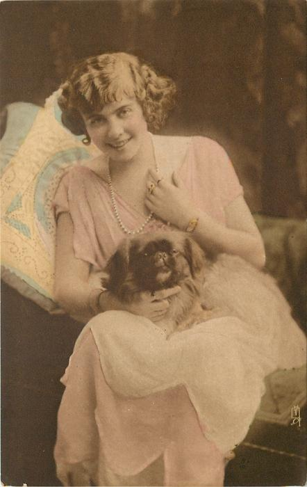 young lady sits looking & facing forward, left hand touches pearls, holding pekingese dog on lap, dog looks front