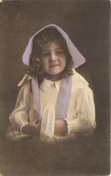 young girl in bonnet & dress sits facing & looking forward, hands touching in front under tie