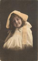 young girl in bonnet & dress sits facing half left, looking forward, arms at sides