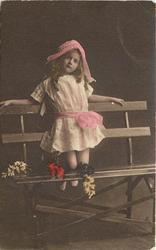 girl in lacy dress & bonnet sits on slatted wooden bench strewn with flowers, she kneels on seat with legs folded back, faces & looks front, arms outstretched along top slat