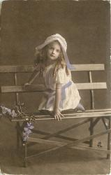 girl in lacy dress & bonnet sits on slatted wooden bench strewn with flowers, both legs on bench and pointing to right, holds bonnet ribbon in left hand
