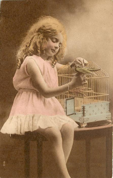 girl sits on table to right of bird cage with open door & stuffed bird perched on top