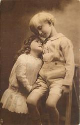 young children & wooden step-ladder, boy sits looking down, girl stands below to left looking up at him, her right hand on his leg, his left hand down at his side