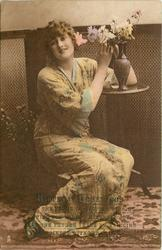 lady in Japanese dress sits on low stool, with arm on table,both hands under flowers, flowers to her left