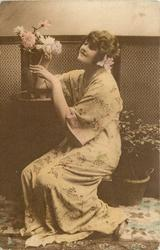 lady in Japanese dress sits on low stool, with arm on table,both hands under flowers, faces left, flower on left side of picture